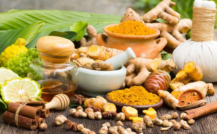 Turmeric powder,Turmeric in Mortar Grinder drugs and ingredient herbs on wooden background